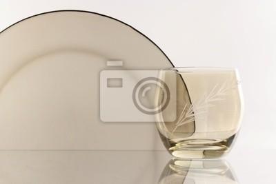 Стакан рядом с стек белых пластин - на белом фоне