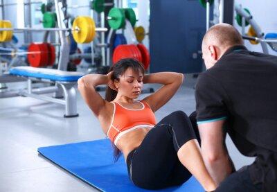 Картина Молодая женщина с ее тренером в тренажерном зале