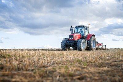 Картина Сельскохозяйственной техники на переднем плане, выполняющей работу в полевых условиях.