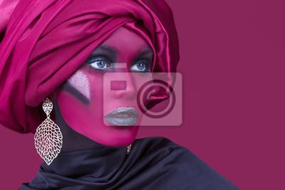 Autiful молодая женщина с волосами, завернутый в тюрбан. Творческий портрет на красном фоне.