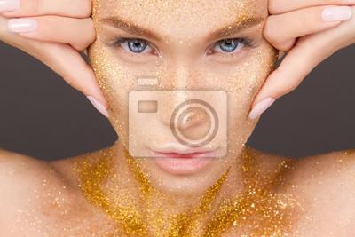 Красота портрет мило прекрасная молодая женщина с блестками на ее лице на сером фоне