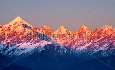 Картина крупным планом красноватых горных вершин во время захода солнца