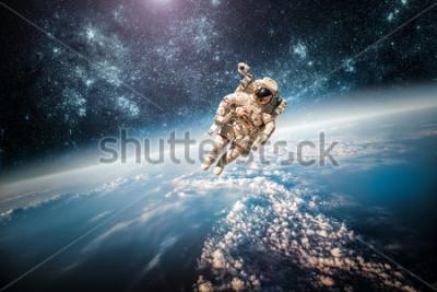 Картина Астронавт в космосе на фоне планеты Земля. Элементы этого изображения предоставлены НАСА.