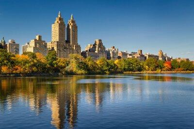Картина Центральный парк и Манхэттен, Upper West Side с красочной осенней листвой. Ясное голубое небо и здания Central Park West, отражающиеся в Жаклин Кеннеди Онассис водохранилище. Нью-Йорк.