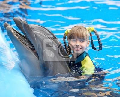 Ребенок и дельфин в голубой воде.