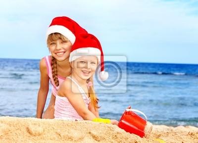 Дети в Санта шляпа, играя на пляже.