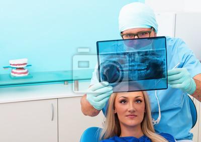 Стоматолог показывает пациента рентген