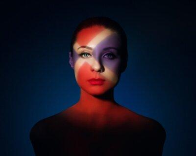 Мода художественный портрет элегантной обнаженной молодой женщины с цветной свет на ее лице