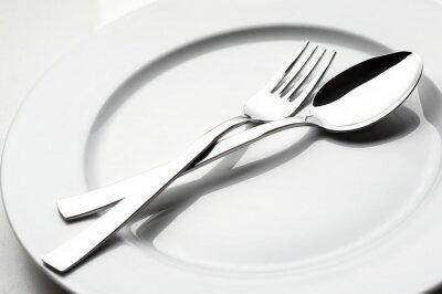 Картина вилки и ложки на белой тарелке