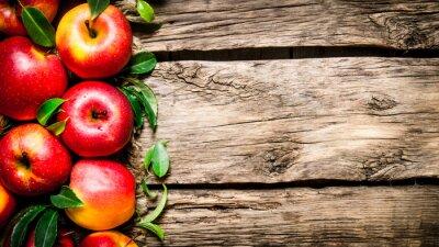 Картина Свежие красные яблоки с зелеными листьями на деревянном столе.