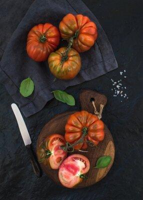 Картина Свежие спелые помидоры hairloom и листья базилика на деревенском деревянной доске на черном фоне каменных.