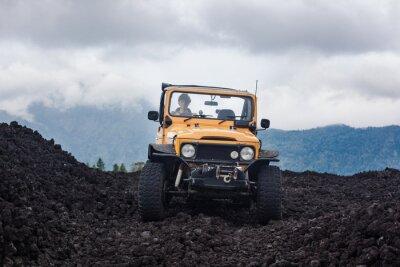 Картина Вид спереди кудрявого водителя в желтом внедорожнике, припаркованном на вершине долины с вулканическими породами и горами на Бали, Индонезия