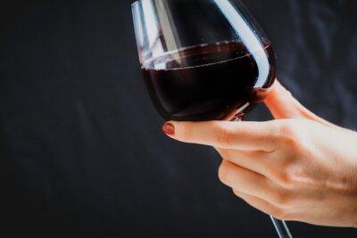 Картина Рука стакан красного вина на темно-сером фоне