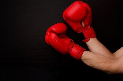 Картина Рука в красный боксерские перчатки в углу кадра на черном фоне, пустое пространство
