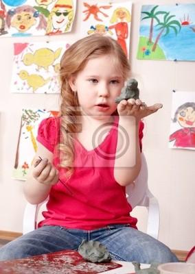 Малыш, играя с глиной.