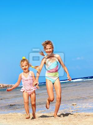 Дети, взявшись за руки, работающих на пляже.