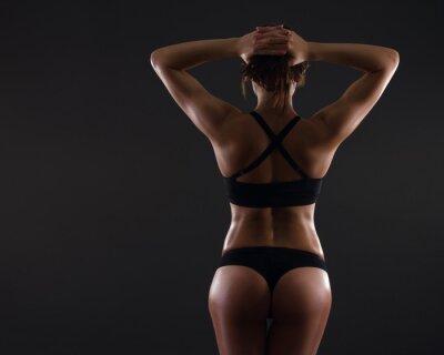Мышечная молодая женщина, стоя на сером фоне.