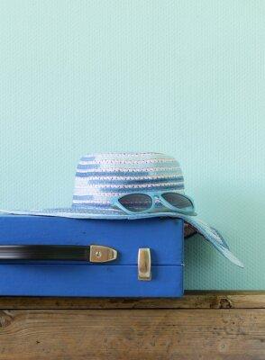 Картина старомодный синий чемодан для путешествий и пляжного шляпе