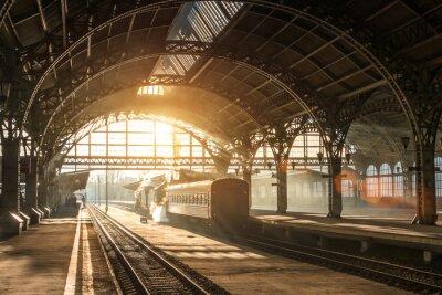 Картина Старый железнодорожный вокзал с поездом и локомотивом на перроне в ожидании отправления. Вечерние лучи солнца в дымовых арках.