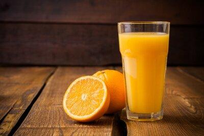 Картина Оранжевые фрукты и стакан сока на коричневом фоне деревянных
