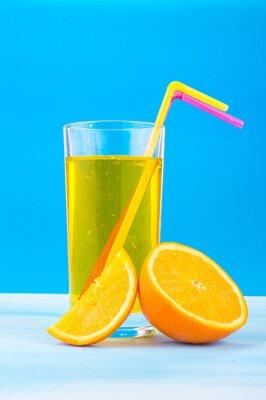 Картина апельсиновый сок в стакане с цветными соломки и дольками апельсина на синем фоне