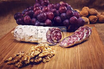 Картина салями с орехами на деревянном блюде с виноградом