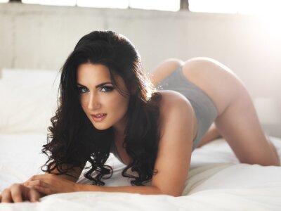 Картина сексуальная модель на ярко освещенной кровати в эротические позы