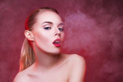 Курение сексуальная молодая женщина на красном фоне.
