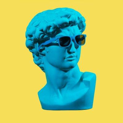Картина Statue. Earphone. Isolated. Gypsum statue of David's head. Man. Creative. Plaster statue of David's head in blue sunglasses. Minimal concept art.