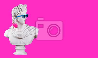 Statue. Earphone on a pink background. Gypsum statue of David's head. Creative. Plaster statue of Apollo's head in blue sunglasses. Minimal concept art.