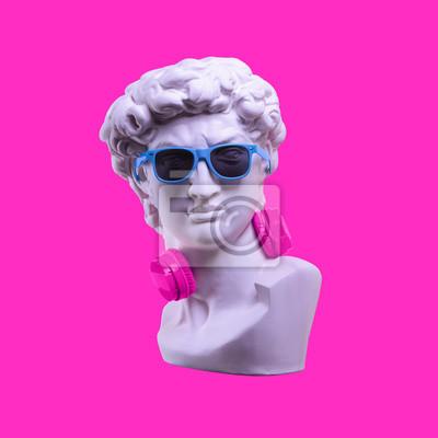 Statue. Earphone on a pink background. Gypsum statue of David's head. Creative. Plaster statue of David's head in blue sunglasses. Minimal concept art.