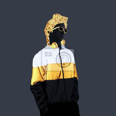 Statue male. Gold earphones on a grey background. Gypsum statue of David's head. Creative. Plaster statue of Apollo's head in gold sunglasses. Minimal concept art collage.