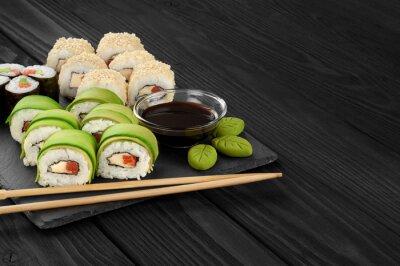 Картина Суши-роллы с авокадо, лососем и кунжутом на сланце лотке.