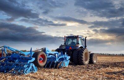 Картина Трактор, работающий в поле на закате