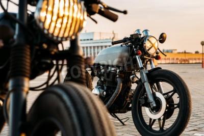 Картина Урожай кастом кафе гонщик на мотоцикле с лампой освещения включен. Один с грилем фары другой с лентой крест над оптикой на пустой парковки на крыше много во время заката. Hipster образ жизни.