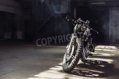 Картина Винтажный мотоцикл, стоящий в темном здании в лучах солнечного света. Тонированные цвета. Передний план