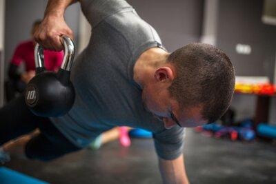 Картина Молодой человек подъема гантели и гири в фитнес-центре