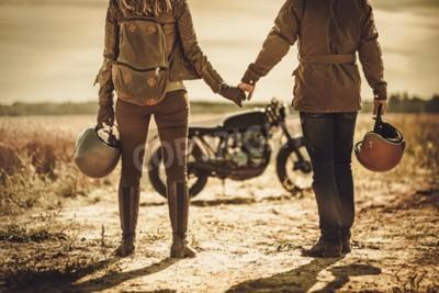 Картина Молодая, стильная пара-гонщик кафе на старинных мотоциклах в поле.