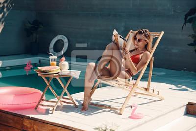 Фотообои Attractive young woman in bikini reading magazine while sunbathing on the poolside outdoors