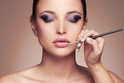 Фотообои Красивая женщина лицо. красоты девушка с идеальной make-up.Makeup художник применяет lipstick.cosmetics