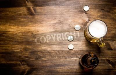 Фотообои Пиво style- бутылка, пиво в стекле и охватывает на деревянный стол.