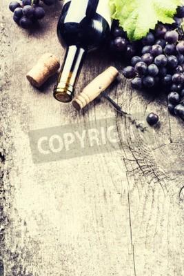 Фотообои Бутылка темного вина, винограда и пробками на фоне старых деревянных
