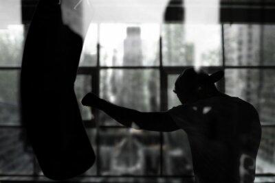Фотообои Boxer hits a punching bag against the window, training