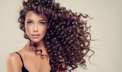 Фотообои Брюнетка с длинными и блестящими вьющимися волосами. Красивая модель с волнистой стрижкой.
