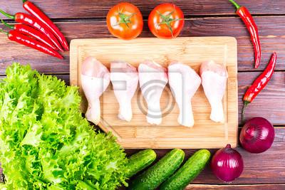 Куриные ноги и овощи на старом столе: помидоры, огурцы, перец, лук, листья салата