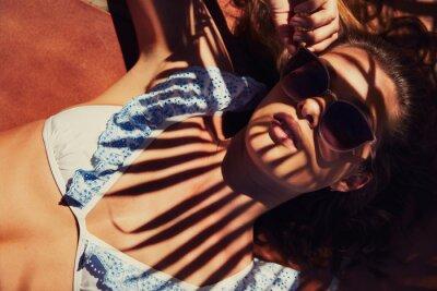 Фотообои Cool girl sunbathing in bikini top and shadows