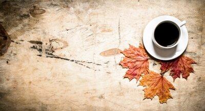 Фотообои Чашка горячего кофе с осенними листьями.
