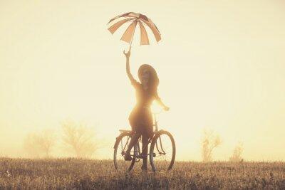 Фотообои Девушка с зонтиком на велосипеде в сельской местности в время восхода солнца