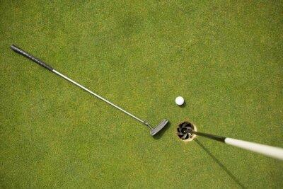 Фотообои Golf club and golf ball on the putting green beside flag