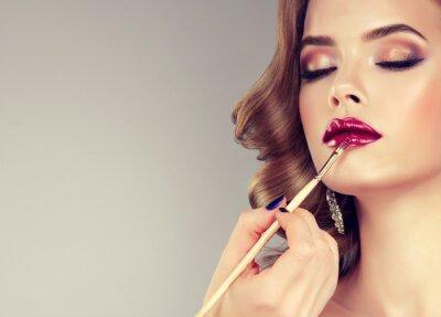 Фотообои Рука макияж мастера, живопись губы молодой красивой модели. Макияж в стадии разработки.